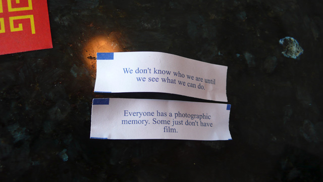 Two fortunes from cookies at a chinese restaurant. The fortunes read: [We don't know who we are until we see what we can do.] and [Every one has a photographic memory. Some just don't have film.]